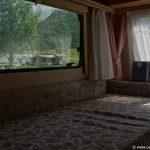 Bett mit Blick aus dem Wohnwagen-Fenster Richtung Berge